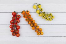 Divers bouquet de tomates sur fond en bois — Photo de stock