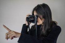 Женщина фотографируется с ретро-камерой — стоковое фото
