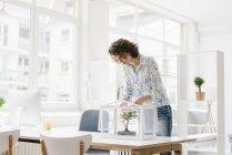 Donna d'affari che si prende cura di albero bonsai — Foto stock