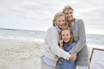 Mother with daughter and grandmother standing on beach — Stock Photo