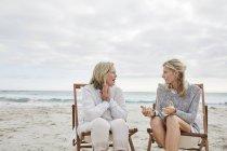 Mutter und Tochter sitzen in Liegestühlen — Stockfoto