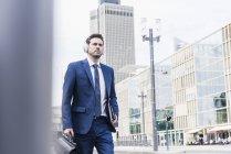 Businessman walking in city — Stock Photo