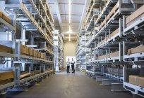 Men interacting in factory warehouse — Stock Photo