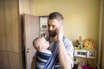 Отец с маленьким сыном разговаривают по телефону — стоковое фото