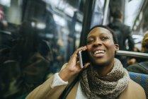 Woman using phone in underground train — Stock Photo