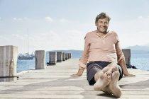 Людина, що сидить на пристані — стокове фото