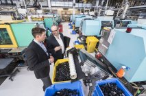 Мужчины рассматривают продукцию на заводе — стоковое фото