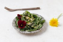 Салат из одуванчиков с рогатой фиалкой и пухлым квиноа — стоковое фото