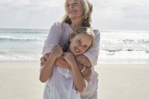 Grandmother embracing granddaughter on beach — Stock Photo