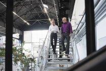 Hommes d'affaires avec tablette descendant les escaliers — Photo de stock