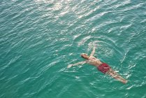 Man floating in turquoise water — Stock Photo