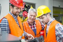 Three men in factory talking with industrial robot in background — Stock Photo