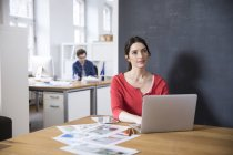 Woman using laptop on table — Stock Photo