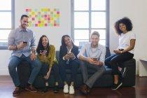 Kollegen sitzen mit Mobiltelefonen — Stockfoto