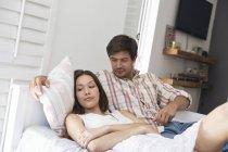 Молодая пара лежит в постели — стоковое фото