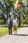 Senior couple with balloons strolling — Stock Photo