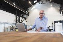 Mann, sitzend mit Laptop und plan — Stockfoto