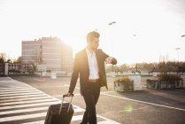 Uomo d'affari che cammina con la valigia di rotolamento — Foto stock