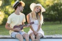 Человек играет укулеле с его подругой — стоковое фото