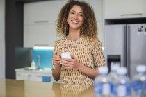Mulher no escritório cozinha segurando copo — Fotografia de Stock