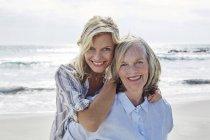 Мать и дочь обнимаются на пляже — стоковое фото