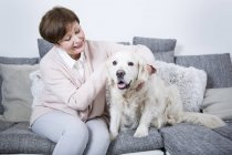 Senior woman sitting with dog — стоковое фото