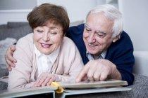 Senior couple watching photo album — Stock Photo