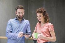 Homem e mulher com telefone e xícara de café — Fotografia de Stock