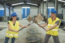 Usine playfighting d'ouvriers avec des pelles — Photo de stock