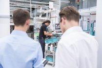 Hommes d'affaires regarder l'homme travaillant dans l'usine — Photo de stock