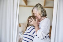 Grandmother kissing granddaughter — Stock Photo