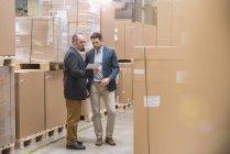 Dois homens olhando para tablet no armazém da fábrica — Fotografia de Stock