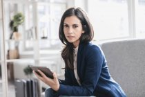 Businesswoman sitting with tablet — Stock Photo