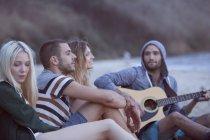Freunde am Strand musizieren — Stockfoto