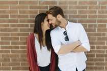 Couple standing in front of brick wall — Stock Photo