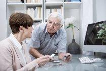 Couple de personnes âgées vérification des dépenses — Photo de stock