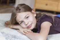 Girl lying on carpet — Stock Photo