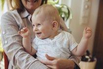 Baby Junge sitzt auf Schoß der Großmutter — Stockfoto