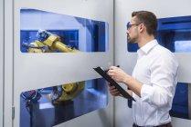 Man taking notes at robotics machine — Stock Photo