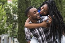 Man giving girlfriend piggyback ride — Stock Photo