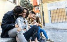 Friends sitting on sidewalk — Stock Photo
