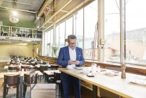 Businessman using cell phone in cafe — Stock Photo