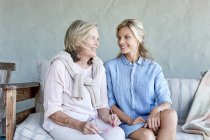 Mother and daughter sitting on couch — Stock Photo