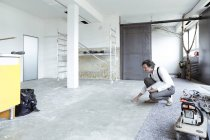Architect checking screed in room — Stock Photo