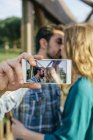 Целовать молодую пару, делая селфи — стоковое фото