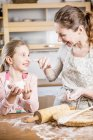Mother and daughter baking bread — Stock Photo