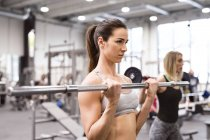 Women lifting weights in gym — Stock Photo
