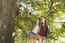 Amies sur swing prendre selfie — Photo de stock