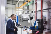 Businessmen examining machine — Stock Photo