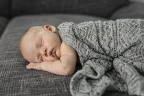 Newborn baby boy sleeping on couch — Stock Photo